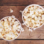 50530835 - popcorn in paper cups on wooden surface. top view